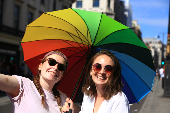two women under a colorful umbrella
