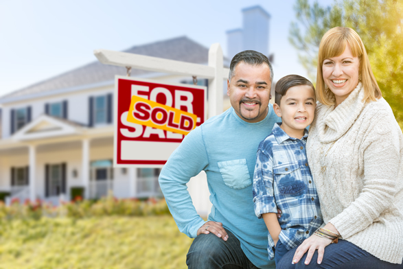 family standing in front of house with a sold sign