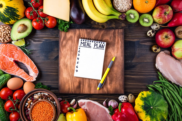 Meal Plan Notebook with healthy types of food surrounding it