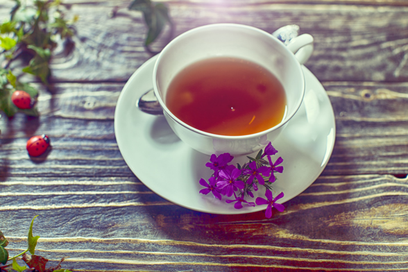cup of tea with purple flowers alongside