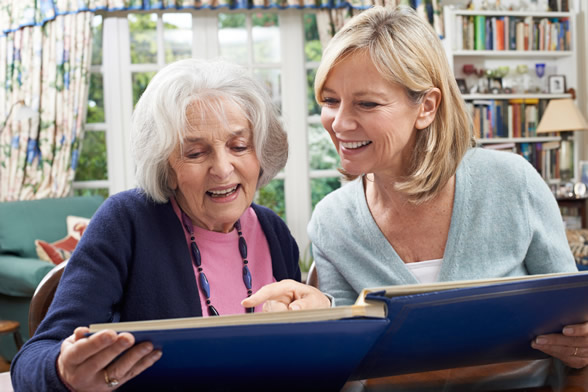 Younger woman viewing photo album with older woman
