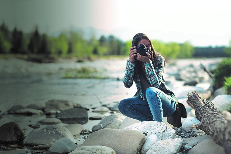 young woman by river with camera