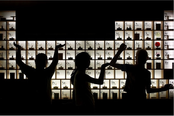 silhouettes of kids stacking items in a large periodic table