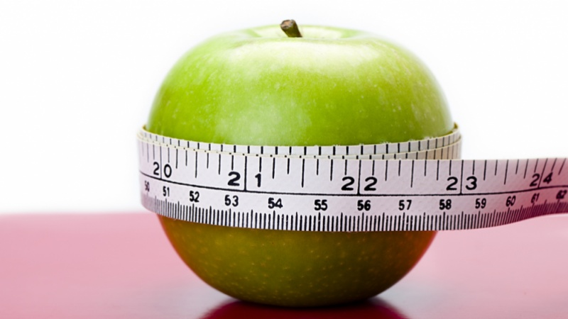 picture of an apple with a tape measure wrapped around it.