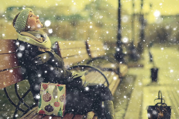 woman sitting on bench watching snow flakes fall
